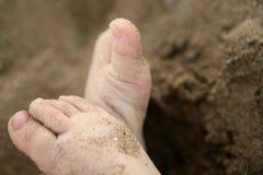 Pies del bebé sobre la arena de la playa Fotografía de archivo libre de regalías