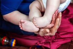 pies del bebé y manos de la madre Fotos de archivo
