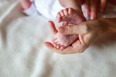 pies del bebé y manos de la madre Foto de archivo libre de regalías