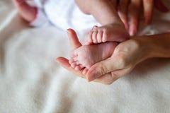 pies del bebé y manos de la madre Fotos de archivo libres de regalías