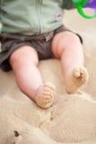 Pies del bebé cubiertos en arena de la playa Fotografía de archivo