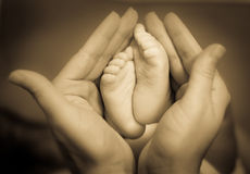 Pies del bebé en las manos de la madre Foto de archivo