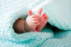 Pies del bebé en manta Fotografía de archivo libre de regalías