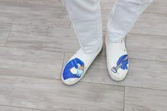 Pies del dentista en zapatos con las imágenes, el tema de la odontología Zapatos profesionales fotos de archivo