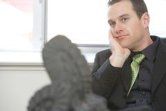 Pies del hombre de negocios en el escritorio que se relaja imágenes de archivo libres de regalías