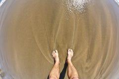 Pies del hombre en la playa Fotografía de archivo libre de regalías