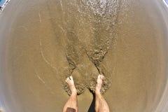 Pies del hombre en la playa Fotos de archivo libres de regalías