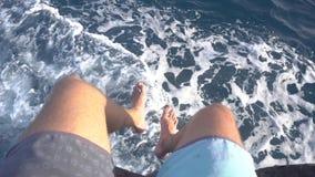 Pies del hombre en un barco móvil sobre el mar metrajes