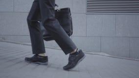 Pies del muchacho bien vestido que caminan en la calle que lleva la bola y que sostiene el monedero Hombre joven serio simultánea metrajes
