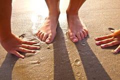 Pies del muchacho en la arena mojada en la playa Foto de archivo libre de regalías