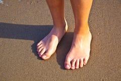 Pies del muchacho en la arena mojada en la playa Imágenes de archivo libres de regalías
