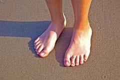 Pies del muchacho en la arena mojada en la playa Fotos de archivo