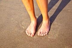 Pies del muchacho en la arena mojada en la playa Fotografía de archivo