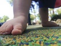 Pies del muchacho sobre el piso de goma Fotos de archivo libres de regalías