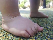 Pies del muchacho sobre el piso de goma Fotografía de archivo libre de regalías
