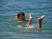 Pies del muchacho y de la muchacha en el mar Imagenes de archivo