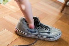 Pies del niño en el zapato adulto fotos de archivo