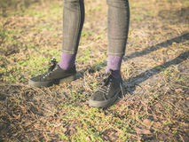 Pies del oand de las piernas de la persona que se colocan en la hierba Imagen de archivo