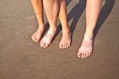 Pies del padre y del hijo en la arena mojada de la playa Fotografía de archivo