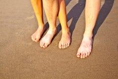 Pies del padre y del hijo en la arena mojada de la playa Fotos de archivo