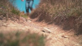 Pies del primer en las zapatillas de deporte funcionadas con en un camino de tierra, caminar y una naturaleza en las montañas almacen de metraje de vídeo