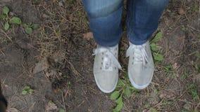 Pies del ` s de la muchacha en los gumshoes grises de las zapatillas de deporte que mueven encendido una tierra almacen de video