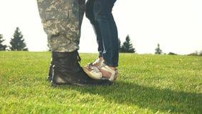 Pies del soldado con las botas y pequeña hija con sandalias metrajes