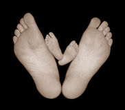 Pies descubiertos del bebé con los pies de la mama Fotos de archivo