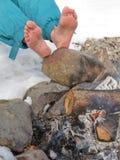 Pies descubiertos que se calientan en una hoguera en invierno Imagen de archivo libre de regalías