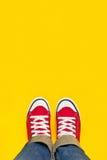 Pies desde arriba, adolescente en las zapatillas de deporte que se colocan en Backgro amarillo Imagen de archivo