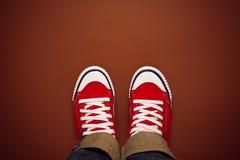 Pies desde arriba, adolescente en las zapatillas de deporte que se colocan en Brown Backgrou Fotos de archivo libres de regalías