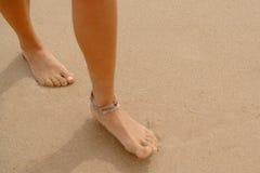 Pies desnudos cubiertos en la arena que camina en la playa Fotografía de archivo