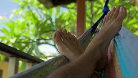 Pies desnudos de balanceo del hombre en una hamaca en terraza Vacaciones en Koh Tao Tanote Bay, Tailandia metrajes