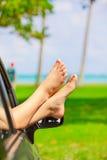 Pies desnudos de la hembra que pegan hacia fuera la ventanilla del coche, por el océano Fotografía de archivo libre de regalías