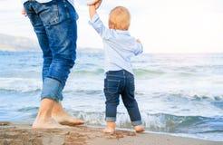 Pies desnudos de niño y de adulto en el mar Concepto de las vacaciones Fotografía de archivo libre de regalías