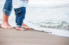 Pies desnudos de niño y de adulto en el mar Concepto de las vacaciones Imagen de archivo libre de regalías