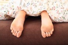 Pies desnudos debajo de la manta Fotos de archivo libres de regalías