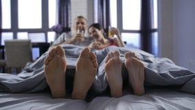 Pies desnudos del primer de pares jovenes debajo de la manta metrajes