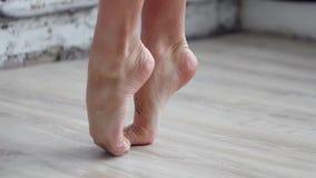 Pies desnudos del ` s de la mujer que calientan colocándose en la extremidad de dedos del pie en piso de madera ligero almacen de video