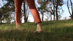 Pies desnudos del ` s de la mujer que caminan sobre campo de hierba verde almacen de metraje de vídeo