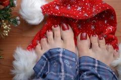 Pies desnudos en el sombrero rojo del Año Nuevo Foto de archivo