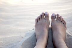 Pies desnudos en la arena blanca caliente Foto de archivo libre de regalías
