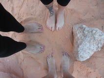 Pies desnudos en la arena roja del desierto Fotos de archivo libres de regalías
