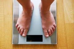 Pies desnudos femeninos con la escala del peso imagen de archivo