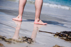 Pies desnudos masculinos en una arena caliente, hombre que toma un paseo en una playa soleada con agua de la turquesa durante vac Imagen de archivo libre de regalías