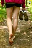 Pies desnudos que caminan a lo largo de cierre de la manera del bosque encima de la foto Fotografía de archivo