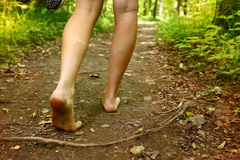 Pies desnudos que caminan a lo largo de cierre de la manera del bosque encima de la foto Imagen de archivo libre de regalías