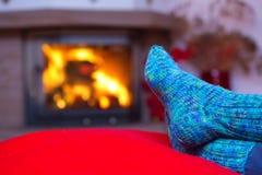Pies en calcetines azules de lana por la chimenea Foto de archivo libre de regalías