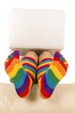 Pies en calcetines coloreados debajo del ordenador portátil Fotografía de archivo