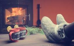 Pies en calcetines de lana por la chimenea de la Navidad La mujer se relaja Foto de archivo libre de regalías